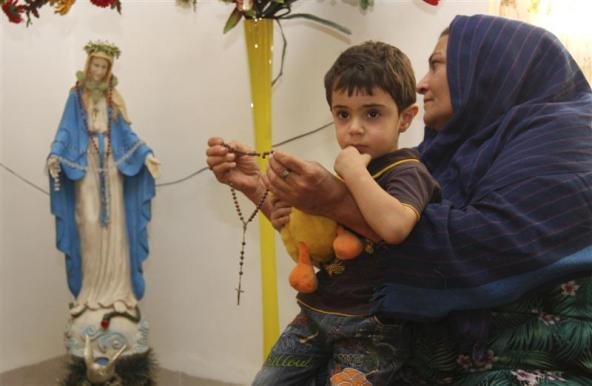An Iraqi Christian refugee woman with a child on her lap holds a rosary as she prays in front of a statue of the Virgin Mary at her house in Arbil, about 300 km (190 miles) north of Baghdad, September 11, 2011.  While most of the sectarian fighting that followed the 2003 U.S.-led invasion has been between Sunni and Shi'ite Muslims, attacks on Christians have increased in recent years. Picture taken September 11, 2011. To match feature IRAQ-CHRISTIANS/ REUTERS/Azad Lashkari     (IRAQ - Tags: RELIGION SOCIETY)